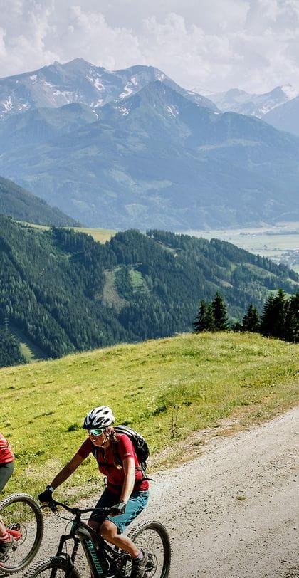 zwei Mountainbiker fahren an einer Bergstraße entlang