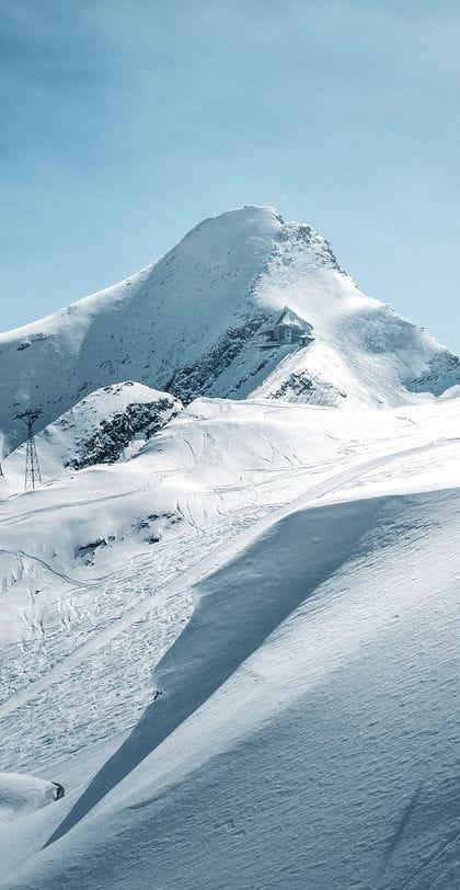 ein Skifahrer fährt im Tiefschnee bei blauem Himmel