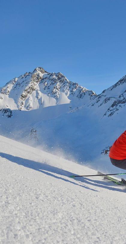 zwei Skifahrer bestreiten eine Abfahrt, im Hintergrund einige Berge