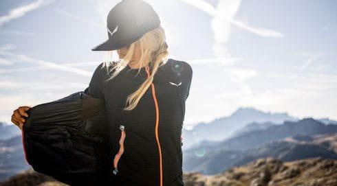 A woman hiking wearing a salewa jacket